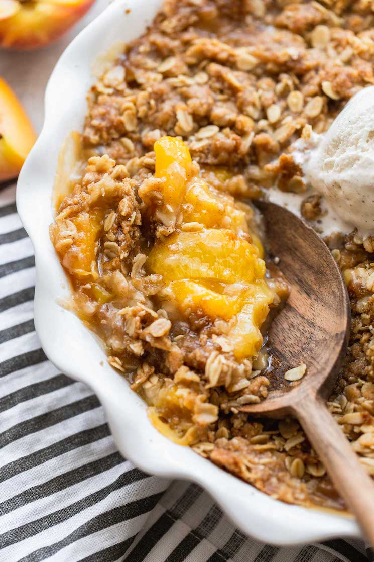 A finished peach crisp in a round baking dish being scooped with a wooden spoon.