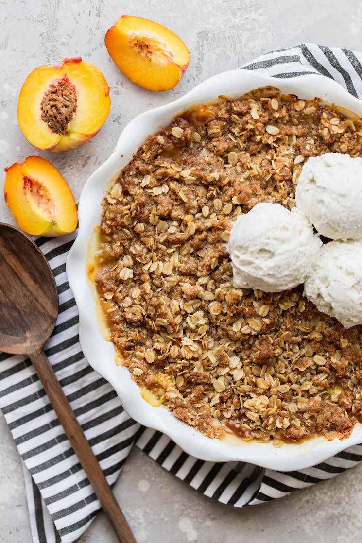 A finished peach crisp in a white baking dish topped with ice cream and another a cut peach beside it.