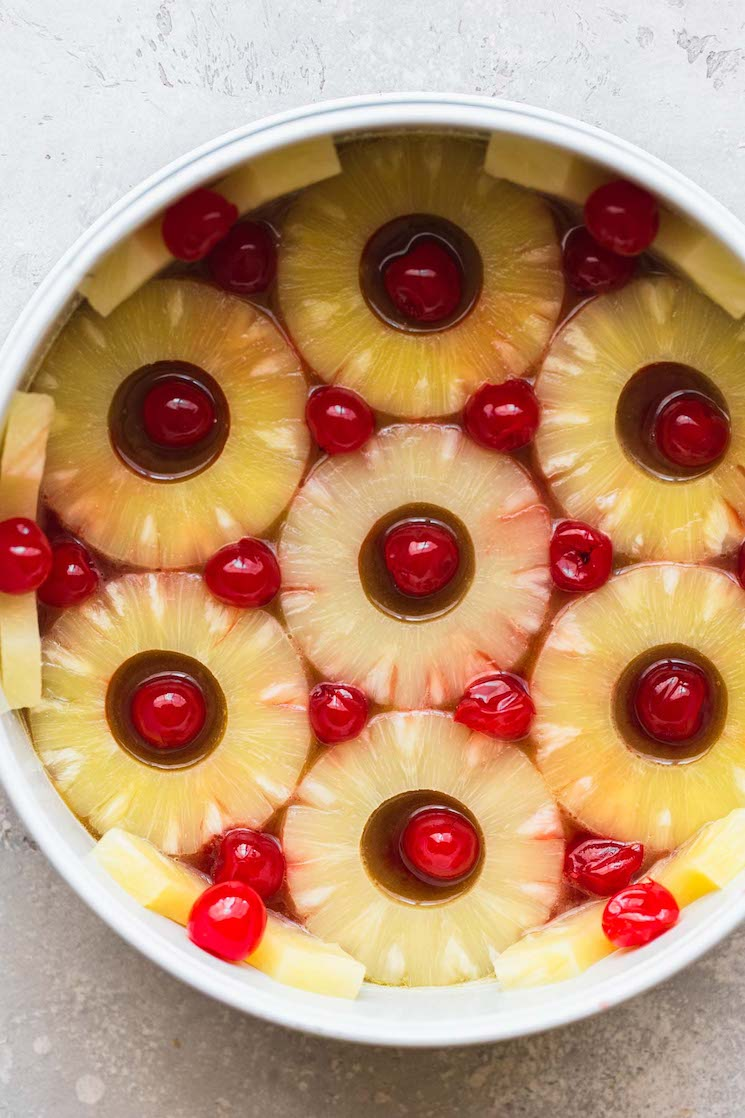 A round cake pan lined with pineapple slices, cherries, and the caramelized sugar topping.