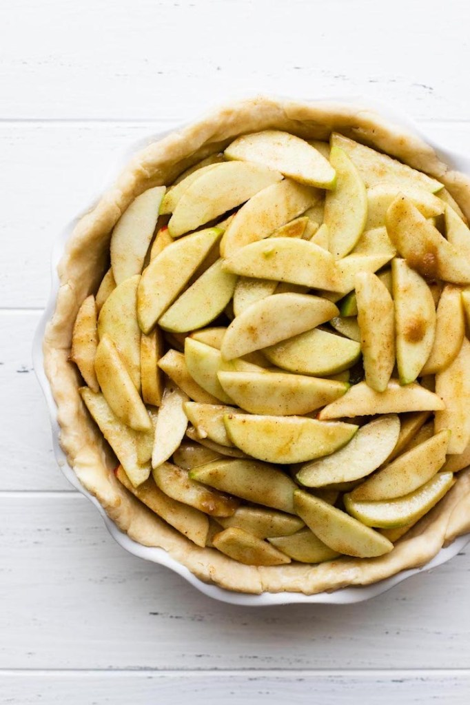 A white pie dish holding a pie crust filled with seasoned sliced apples.