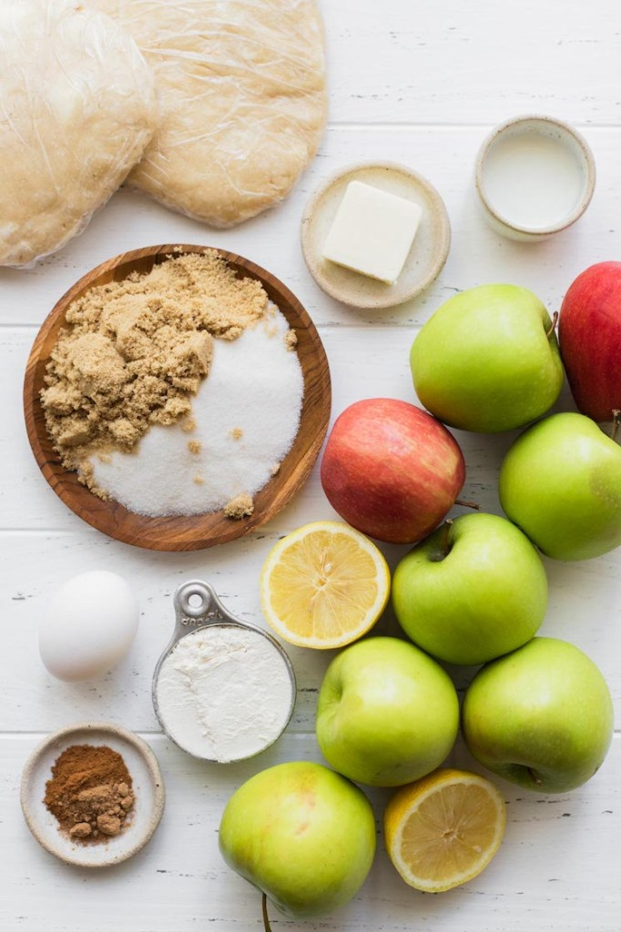 The ingredients needed to make apple pie sitting on top of a white surface.
