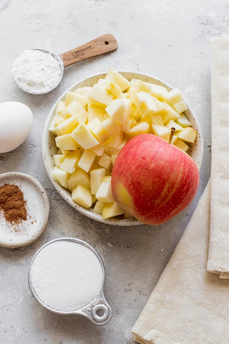 The ingredients for apple turnovers sitting on top of a rustic gray surface.