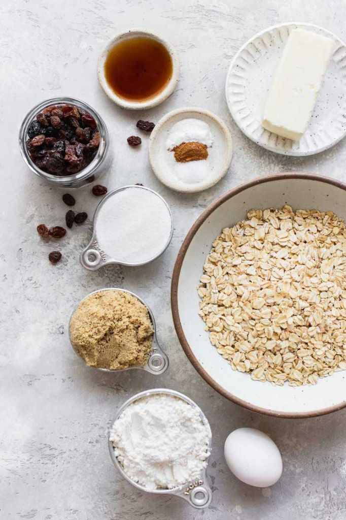 The ingredients needed to make homemade oatmeal raisin cookies laid out in bowls and plates on top of a gray surface.