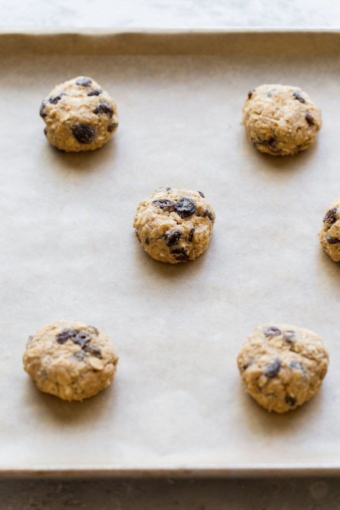 A baking sheet lined with parchment paper holding cookie dough balls that have been pressed down slightly.
