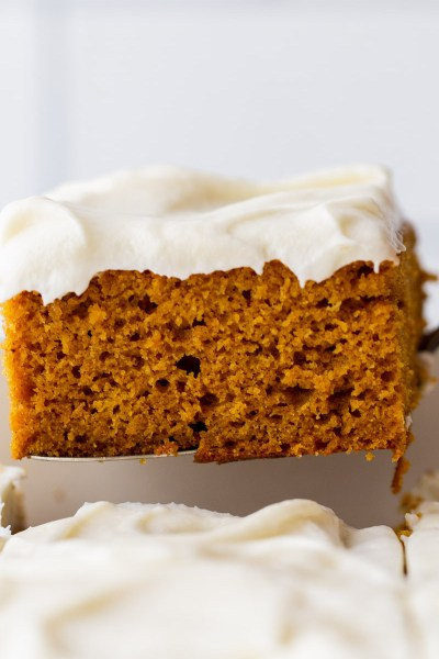 A single piece of cake being removed from the baking dish showing the cake and frosting layers.