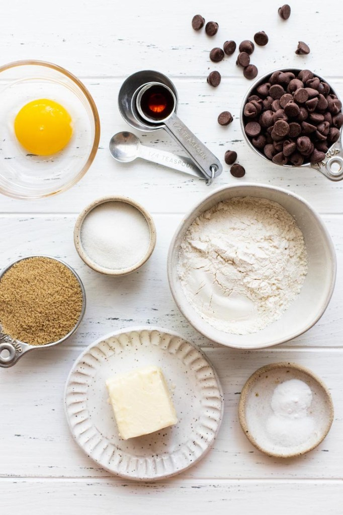 The ingredients needed to make a small batch of chocolate chip cookies sitting on top of a worn white surface.