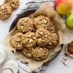 An overhead image of cookies in a metal baking dish surrounded by apples and cinnamon.