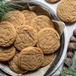 A baking pan lined with parchment paper and filled with soft molasses cookies.