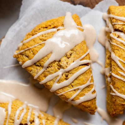 A pumpkin scone topped with maple cinnamon glaze on a piece of parchment paper.