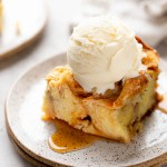 A slice of bread pudding with a scoop of ice cream on top on a white speckled plate.