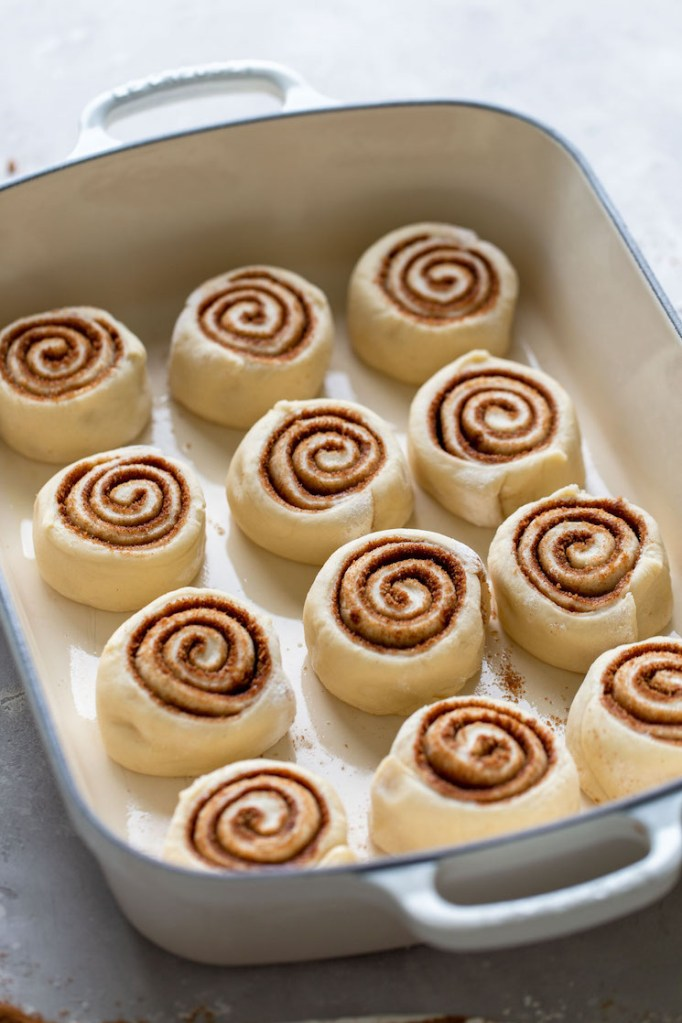 Cinnamon rolls that have been cut and placed into a baking pan.