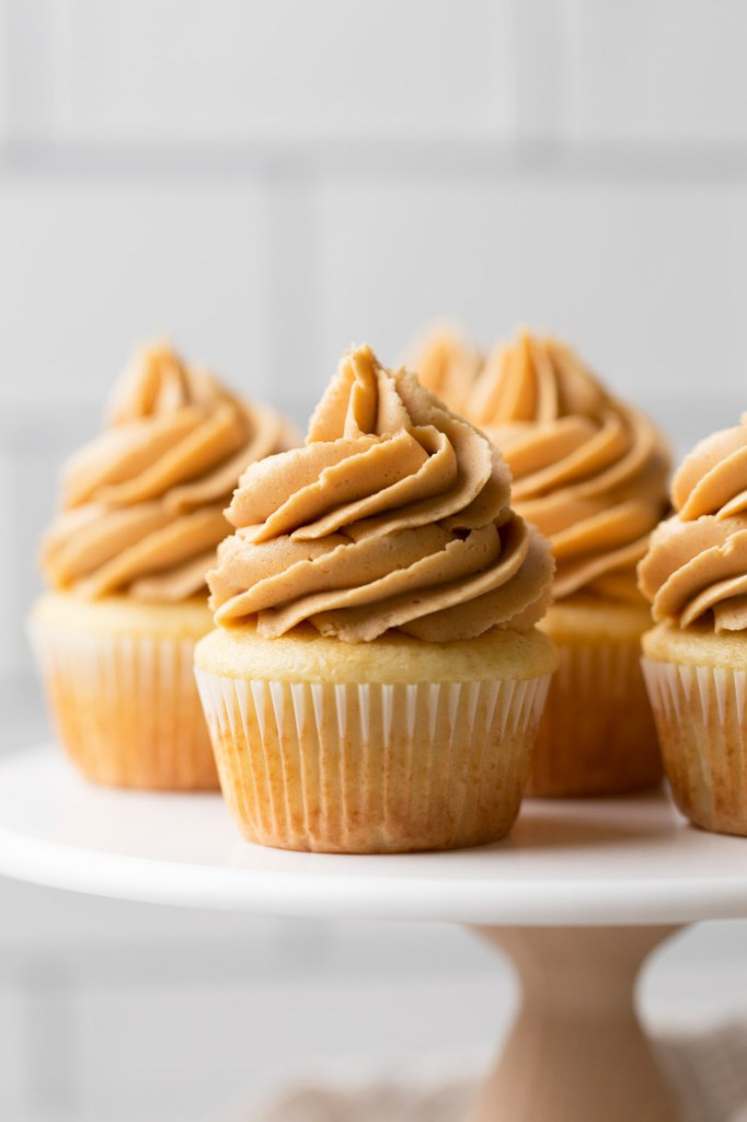 A marble cake stand holding several vanilla cupcakes topped with peanut butter frosting.
