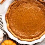 An overhead view of a homemade pumpkin pie in a white pie plate. A mini pumpkin and cinnamon sticks are near it.