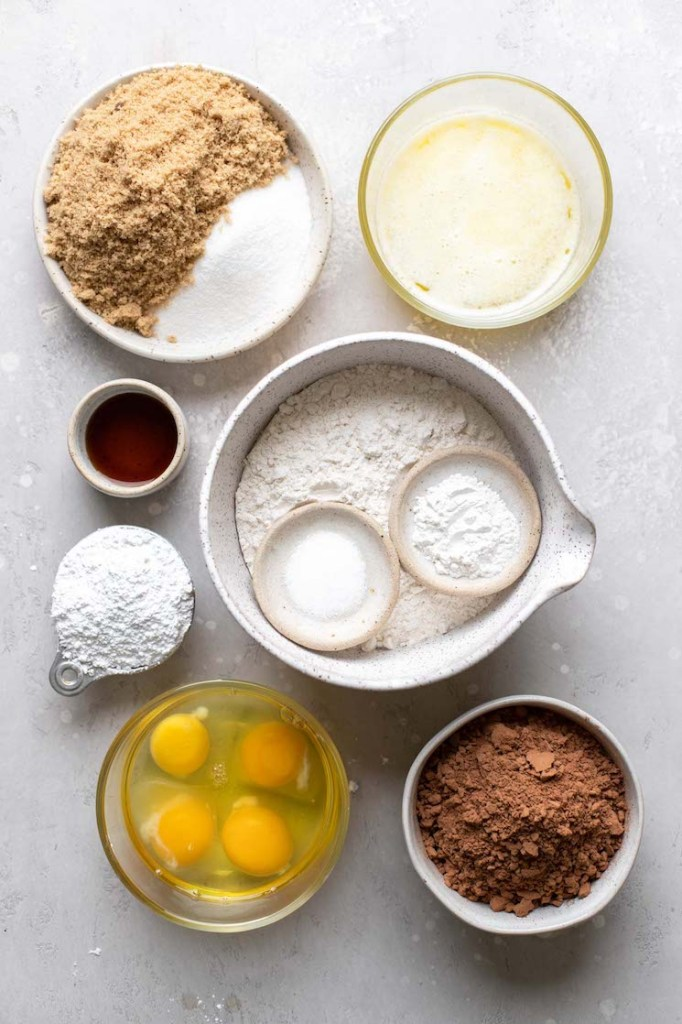 The ingredients needed to make cookies in bowls on top of a rustic gray surface.