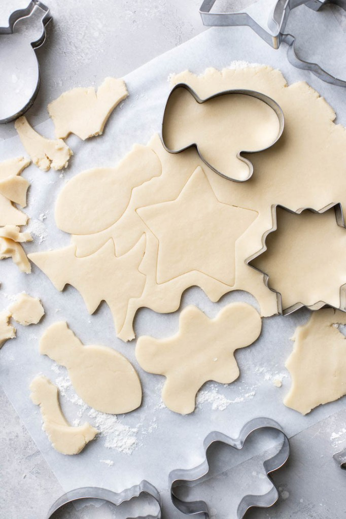 Cookie dough rolled out and cut out into different shapes on parchment paper.