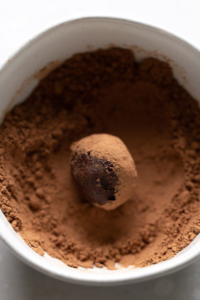 A homemade truffle being coated in cocoa powder.