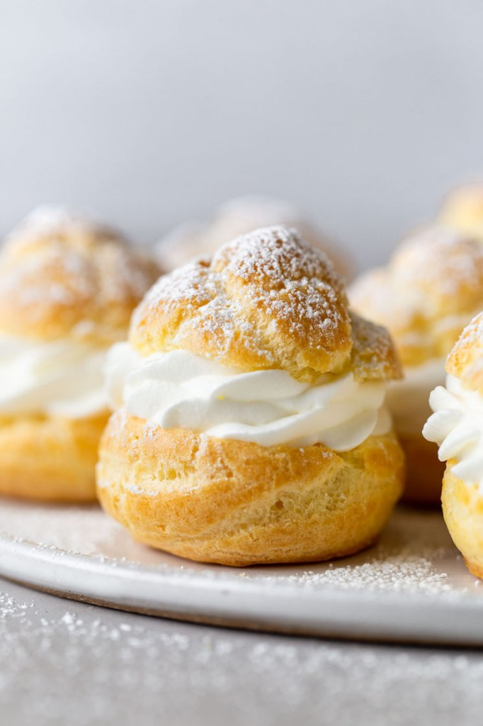 Side view of homemade cream puffs filled with whipped cream on a white plate.
