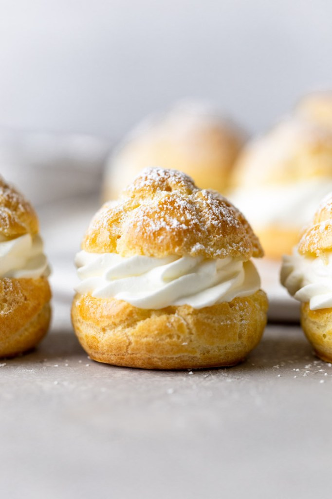 Side view of filled cream puffs lined up on a countertop. More cream puffs rest on a plate in the background.