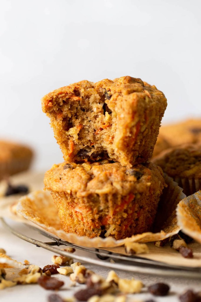 Two morning glory muffins stacked on top of each other, on a wire rack. The top muffin has a big bite missing.