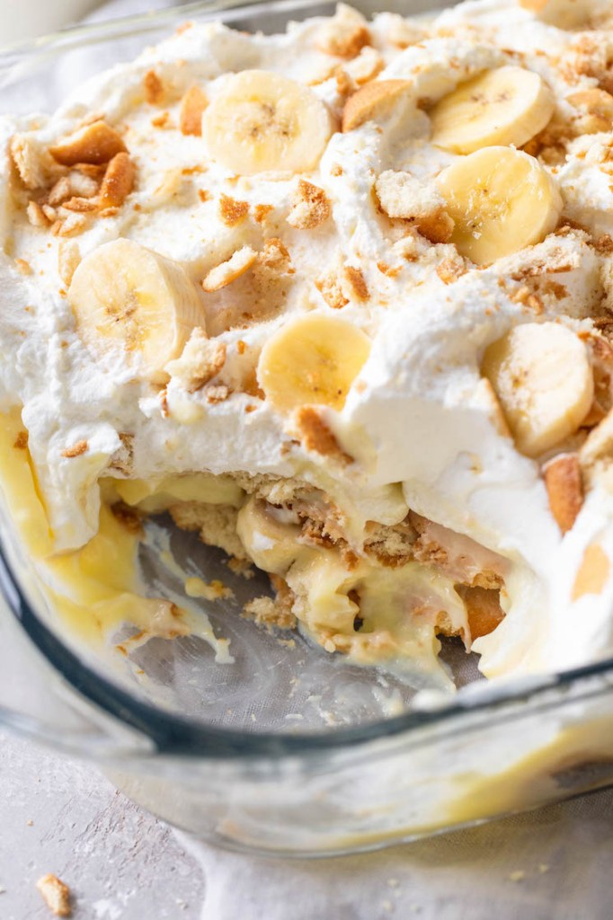 A close up view of a Nilla Wafer banana pudding in a glass dish. A generous serving has been scooped out of the dish.