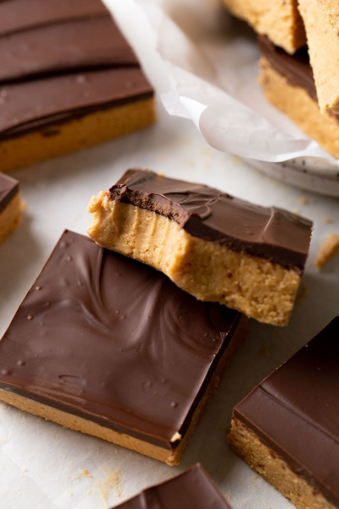 A chocolate peanut butter candy bar with a bite missing resting atop another bar.