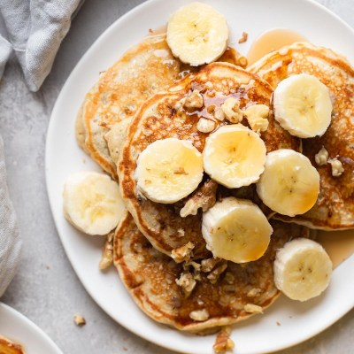 Overhead view of banana pancakes topped with banana slices and chopped walnuts on a white plate.