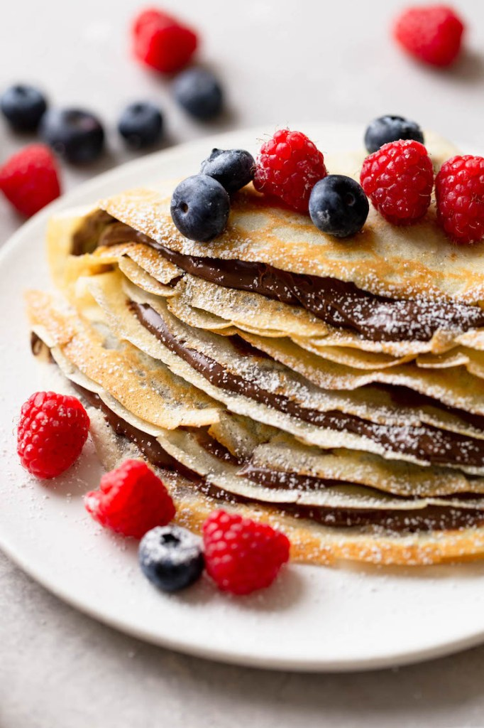 A stack of homemade crepes oozing Nutella and topped with fresh berries. More berries are scattered in the background.