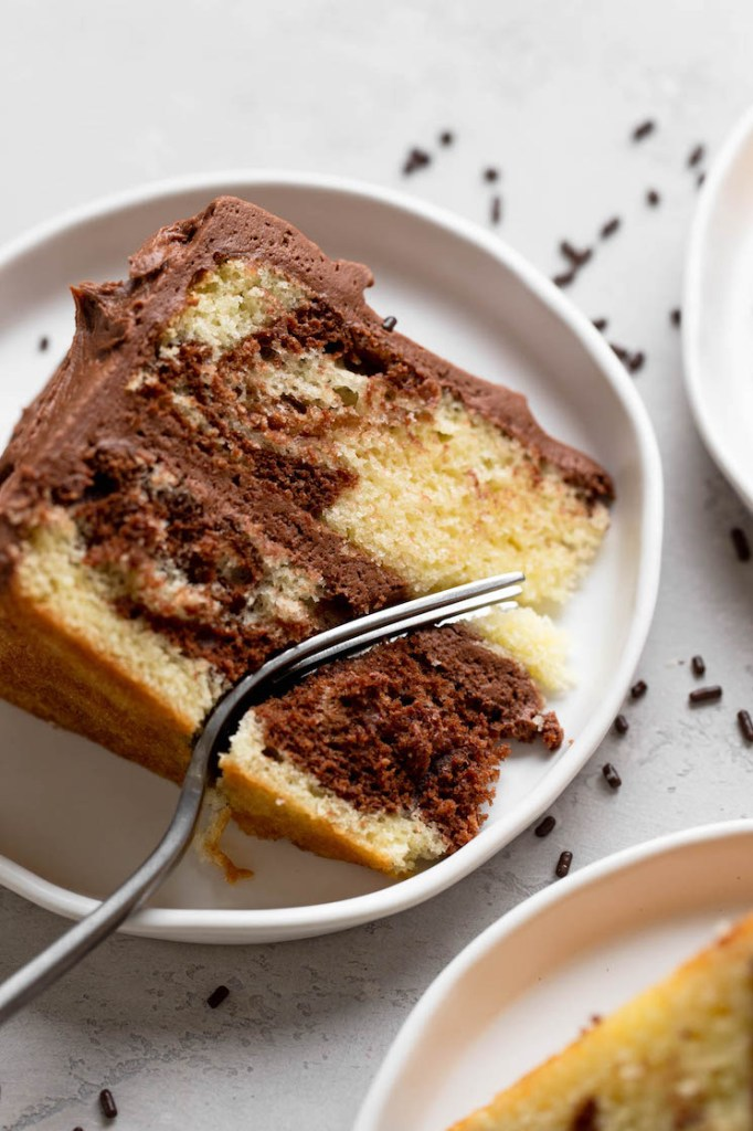 An overhead view of a slice of marble cake on a white plate. A fork is digging into the slice.