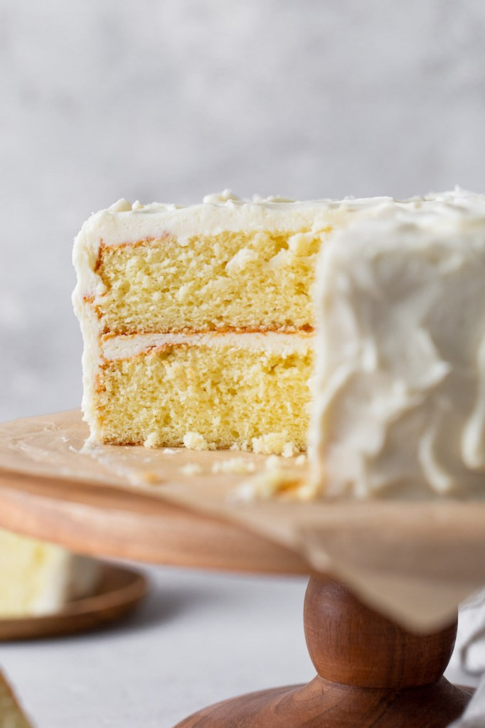 A fluffy vanilla cake frosted with vanilla buttercream, viewed from the side. A slice has already been removed from the cake stand.