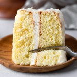 A slice of vanilla cake lying on its side on a wood plate. A fork is digging into the end of the slice.