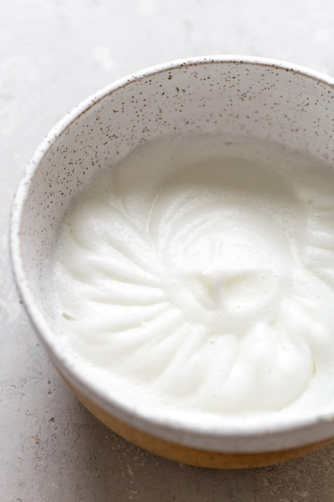 Egg whites beat to stiff peaks in a speckled mixing bowl.