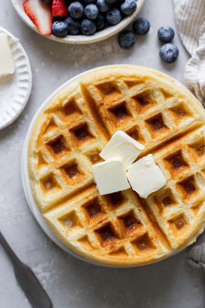 An overhead view of a waffle topped with three pats of butter. A dish of fresh berries rests on the side.