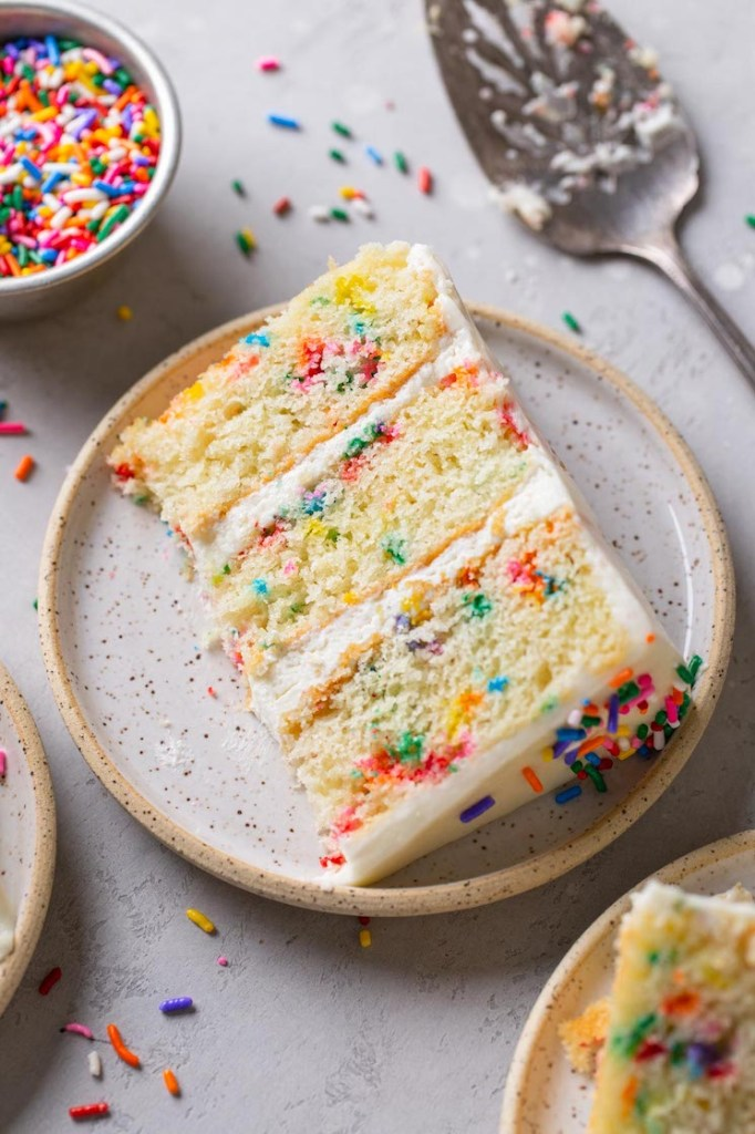 A slice of funfetti layer cake on a speckled white plate.
