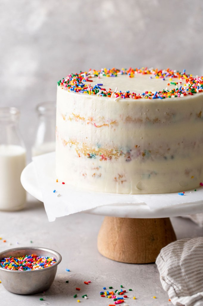 A homemade funfetti cake on a cake stand. Two glass bottles of milk are in the background and a dish of sprinkles is in the foreground.