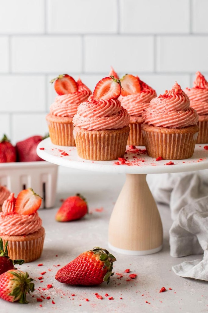 A side view of fresh strawberry cupcakes on a cake stand. Additional cupcakes and fresh berries litter the counter underneath.