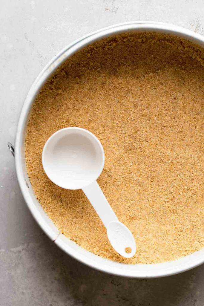 An overhead view of a graham cracker crust in a springform pan. A measuring cup rests on the crust.