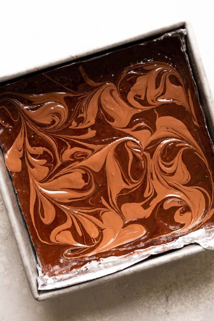 An overhead view of brownie batter that's been swirled with Nutella in a metal baking dish.