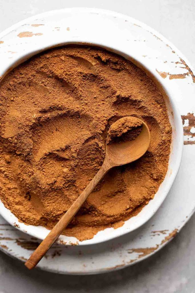 Pumpkin pie spice mixed together on a white plate. A brown spoon rests on top of the spices.