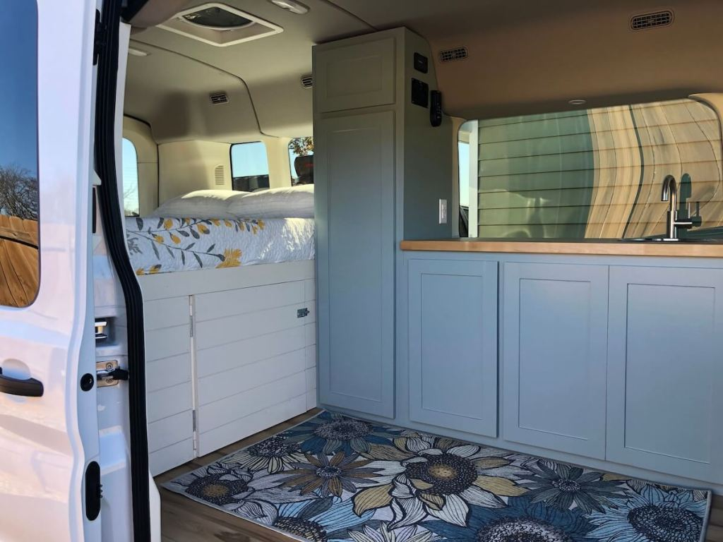 A cargo van that has a bed with storage underneath, blue cabinets, a sink, and a blue rug with flowers on it.