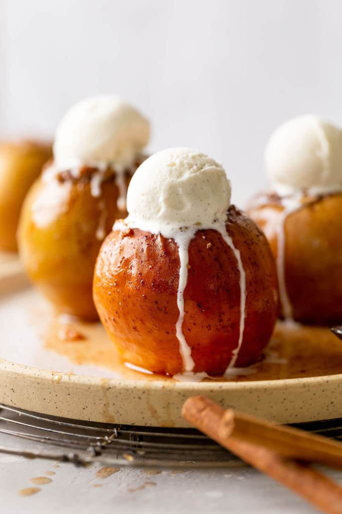 Three stuffed baked apples topped with vanilla ice cream on a speckled white plate.