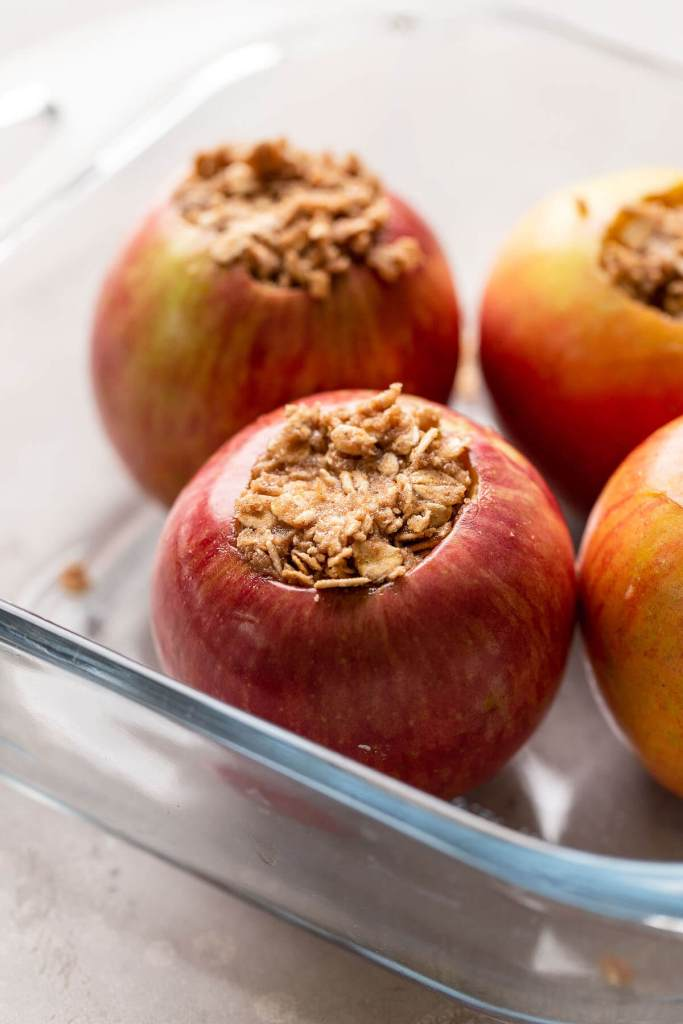 Whole apples in a glass baking dish that have been stuffed with a cinnamon oat mixture.