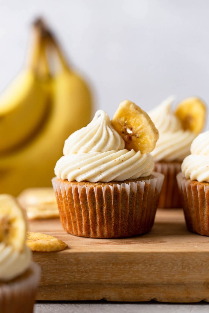 Side view of banana cupcakes with cream cheese frosting on a wooden board. A bunch of bananas rest in the background.