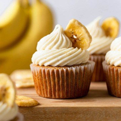 Several banana cupcakes on top of a wooden surface. Banana chips and bananas rest in the foreground and background.