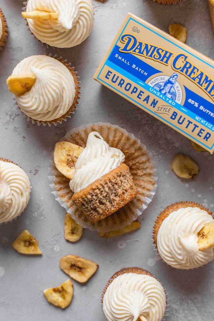 An overhead view of frosted banana cupcakes with a package of Danish Creamery butter. One cupcake is lying on its side.
