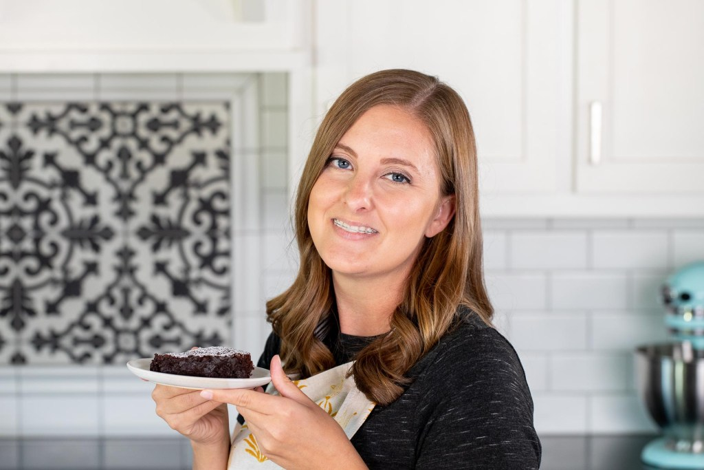 A picture of Danielle in her kitchen holding a plate with a slice of flourless chocolate cake.