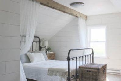 Sheer white curtains hung from wood beam