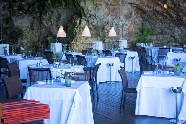 Tables set inside a seaside cave at Grotta Palazzese