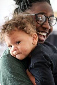 black girl with glasses holding mixed baby boy