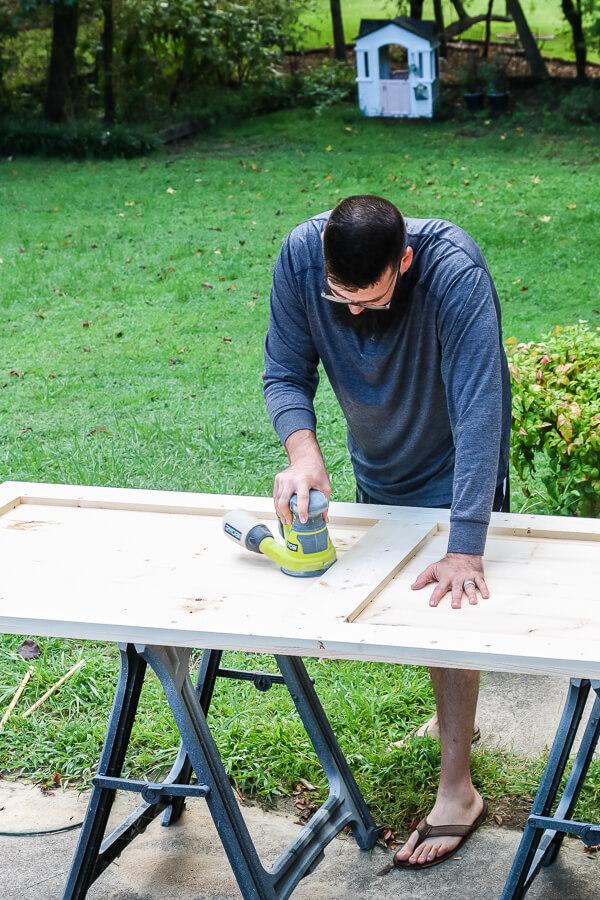 man in long sleeve gray shirt sanding DIY barn door