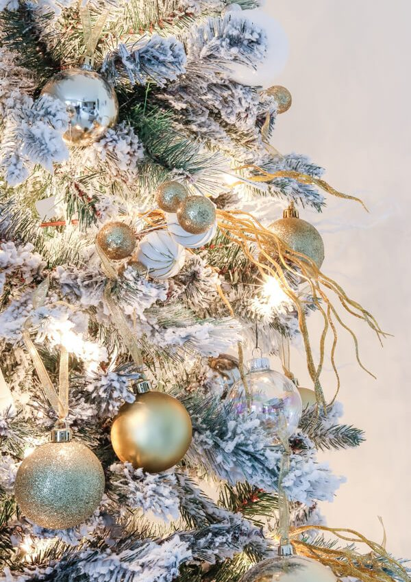 closeup of flocked christmas tree with gold ornaments and picks